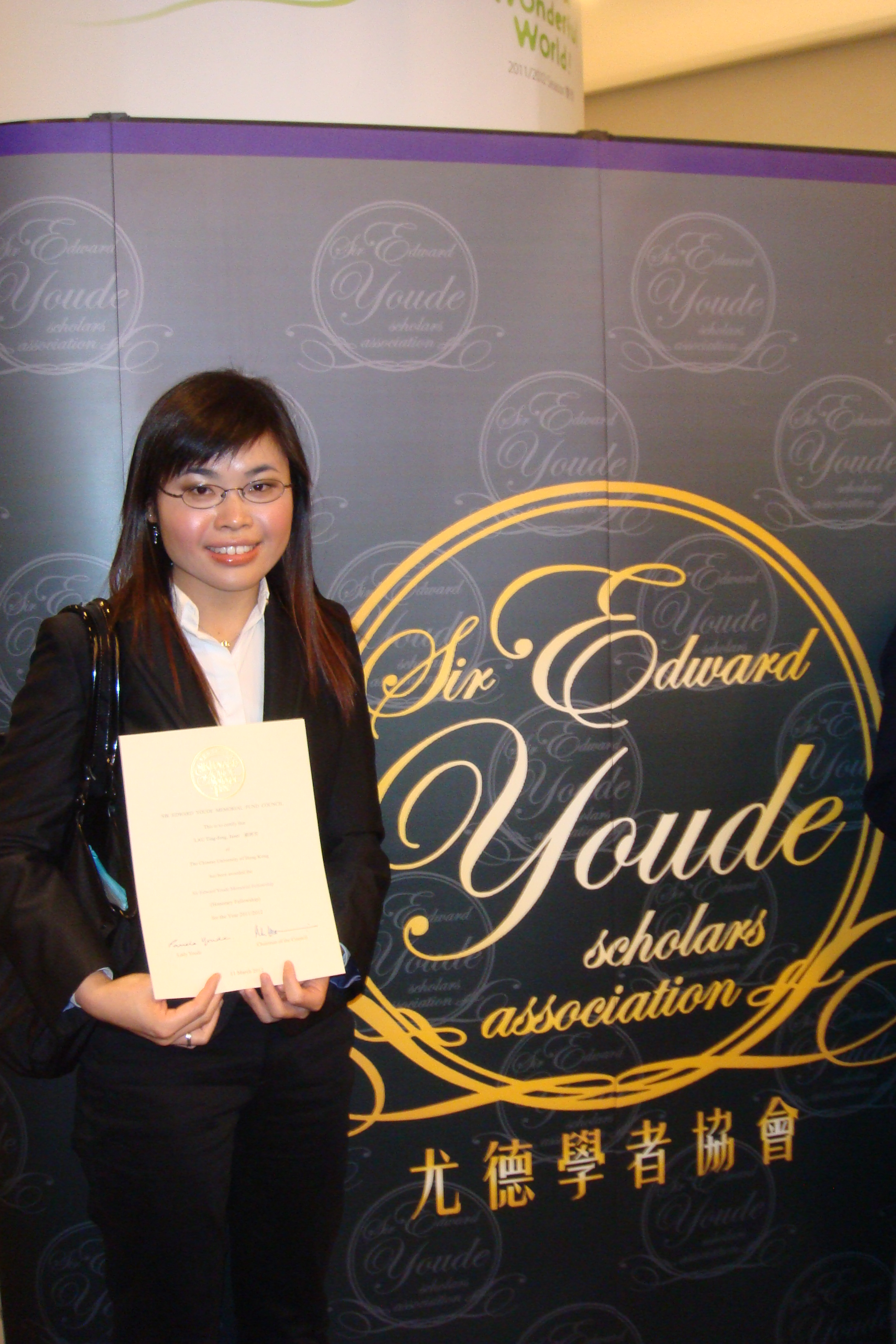 another photo of Ms. Janet Lau Ting Fong and her award certificate
