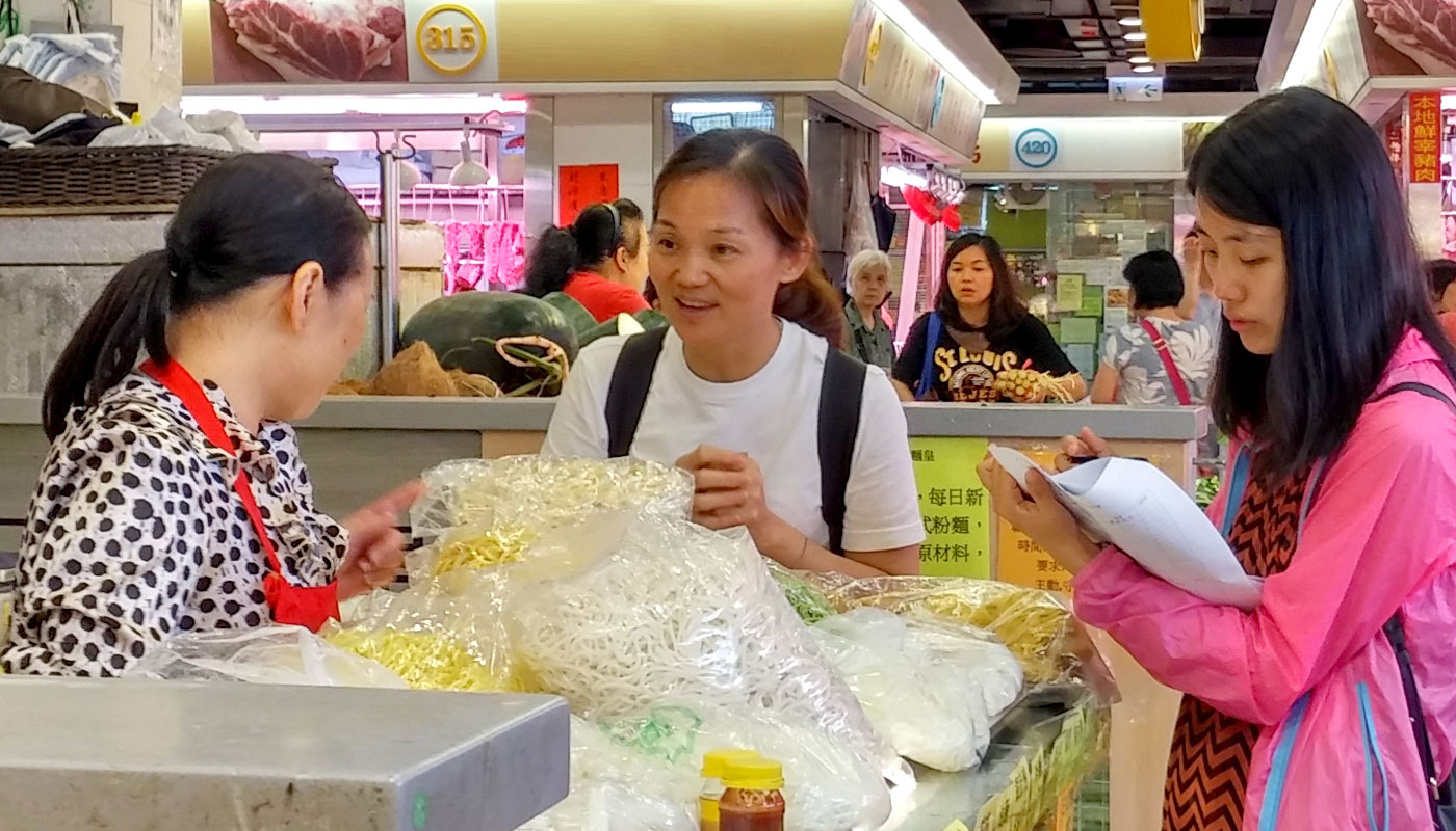 Students team up with a neighbourhood resident to interview tenants at Lok Fu Market