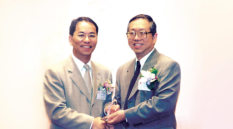 2001年9月于中大数学科学研究所成立「关百豪奖学金」,资助博士生在数学方面研究,国际著名数学家兼研究所所长丘成桐教授颁赠纪念奖牌<em>(受访者提供)</em>